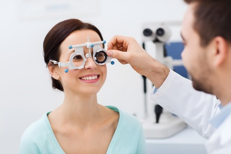 health care, medicine, people, eyesight and technology concept - optometrist with trial frame checking patient vision at eye clinic or optics store Foto de archivo