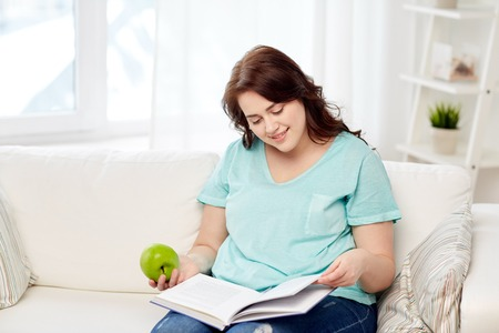 person reading: healthy eating, organic food, fruits, diet and people concept - happy young plus size woman reading book and eating green apple at home Stock Photo