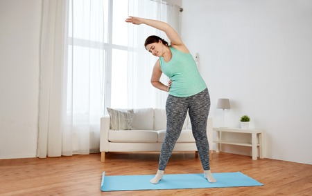 working out: fitness, sport, exercising, training and lifestyle concept - smiling plus size woman stretching on mat at home