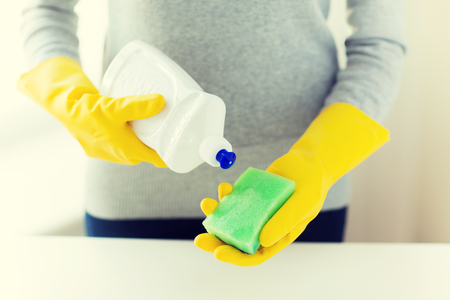 cleanser: people, housework, washing-up and housekeeping concept - close up of woman applying liquid soap from cleanser bottle to sponge at home