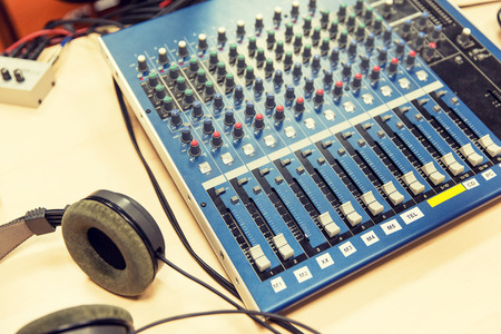 remote controls: technology, electronics and equipment concept - control panel and headphones at recording studio or radio station