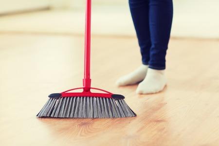 koncepcja ludzie, prace domowe, sprzątanie i sprzątanie - zbliżenie nóg kobiety z miotłą zamiatającą podłogę w domu