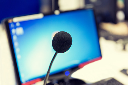 transmitting device: technology, electronics and audio equipment concept - close up of microphone and computer monitor at recording studio or radio station Stock Photo