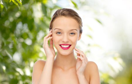 natural beauty: beauty, people and health concept - smiling young woman face with pink lipstick on lips and shoulders over green natural background Stock Photo