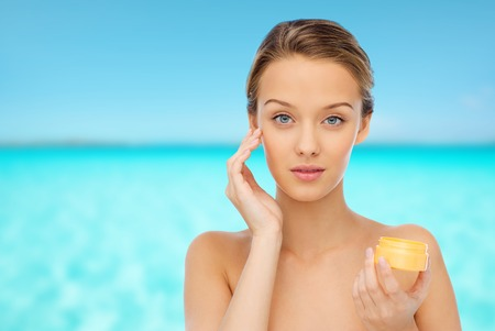 skin care woman: beauty, people, cosmetics, skincare and cosmetics concept - young woman applying cream to her face Stock Photo