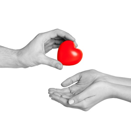 life giving birth: love, relationship, charity and medicine concept - man hand giving red heart to woman Stock Photo