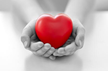 mensen, liefde, liefdadigheid en familieconcept - sluit omhoog van kindhanden thuis houdend rode hartvorm Stockfoto