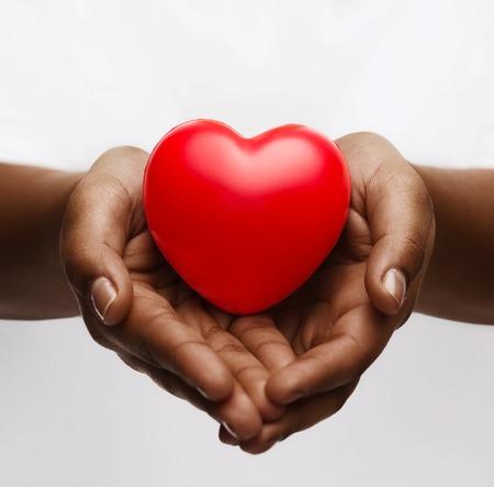 健康、薬および慈善の概念 - 小さな赤いハートとアフリカ系アメリカ人の女性の手のクローズ アップ