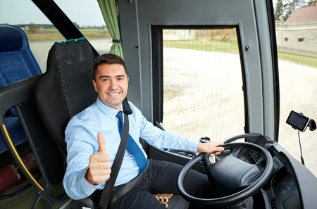 transport, tourism, road trip and people concept - happy driver driving intercity bus and snowing thumbs up