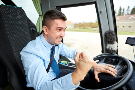 transport, tourism, gesture, emotion and people concept - angry driver showing fist and driving bus Archivio Fotografico