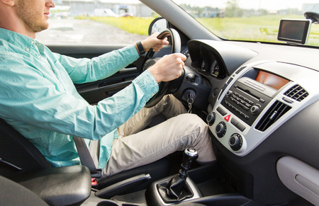 driving a car: transport, business trip, destination and people concept - close up of young man driving car
