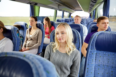travel woman: transport, tourism, road trip and people concept - young woman with group of passengers or tourists in travel bus