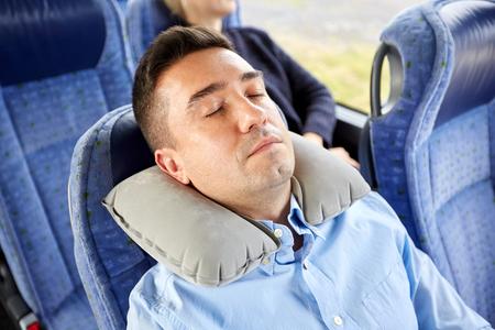 el transporte, el turismo, el descanso, la comodidad y el concepto de la gente - hombre durmiendo en autobús o tren viajes con cuello cervical almohada inflable