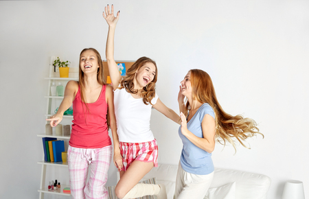 pajama party: friendship, people and pajama party concept - happy friends or teenage girls having fun, dancing and jumping on bed at home