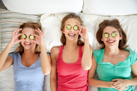 girl home: people, beauty, natural cosmetics and pajama party concept - happy friends or teenage girls with cucumber mask having fun and lying in bed at home Stock Photo