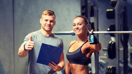 Fitness, sport, oefenen en dieet concept - lachende jonge vrouw en persoonlijke trainer met klembord met duimen omhoog in de sportschool Stockfoto