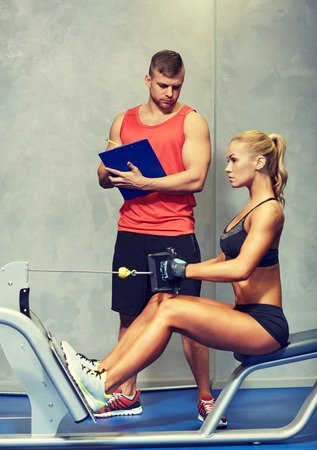 fitness gym: sport, fitness, teamwork and people concept - young woman and personal trainer flexing muscles on gym machine