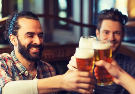 pubs: people, men, leisure, friendship and celebration concept - happy male friends drinking beer and clinking glasses at bar or pub