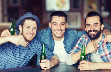 people, leisure, friendship and bachelor party concept - happy male friends drinking bottled beer and hugging at bar or pub Imagens