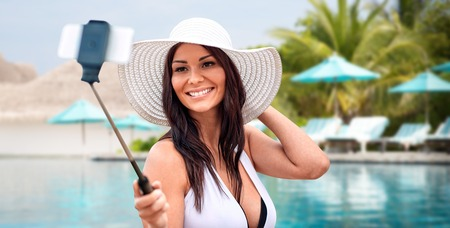 pool stick: lifestyle, leisure, summer, technology and people concept - smiling young woman or teenage girl in sun hat taking picture with smartphone on selfie stick over beach and swimming pool background