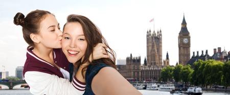 jovenes estudiantes: las personas, los viajes, el turismo y el concepto de la amistad - sonriendo feliz niñas adolescentes que están tomando bastante autofoto y que se besan sobre el fondo londres
