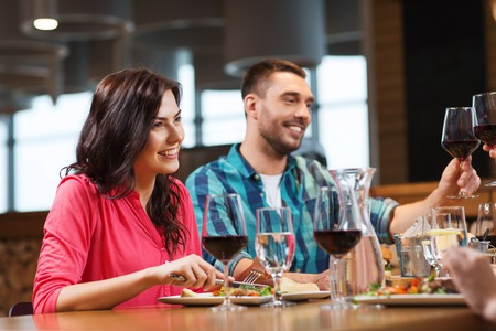 wine glasses: leisure, celebration, food and drinks, people and holidays concept - happy couple and friends clinking glasses of wine at restaurant Stock Photo