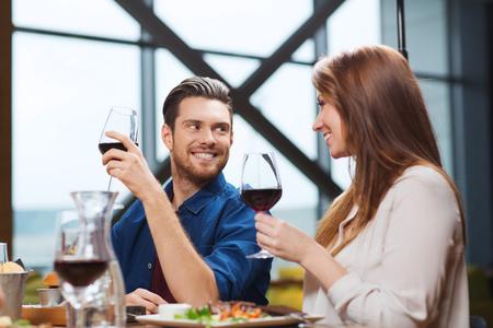 tomando vino: Ocio, Comida, comida y bebida, la gente y el concepto de vacaciones - sonriente pareja cenando y bebiendo vino tinto en el restaurante