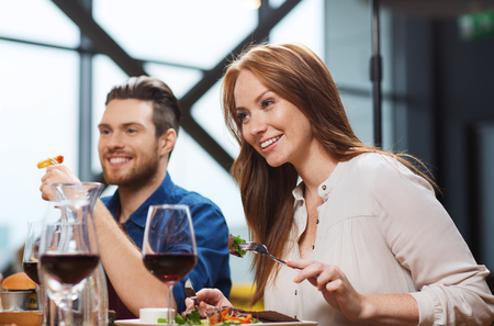 dinner party: leisure, food and drinks, people and holidays concept - happy couple having dinner at restaurant Stock Photo
