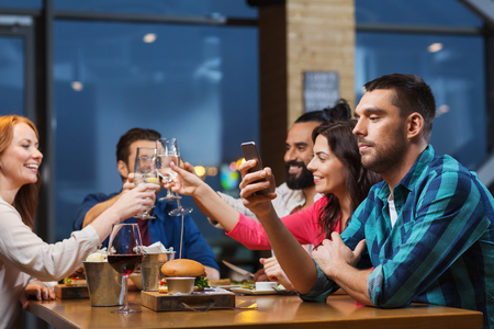 mobile phones: leisure, technology, internet addiction, lifestyle and people concept - man with smartphone and friends at restaurant Stock Photo