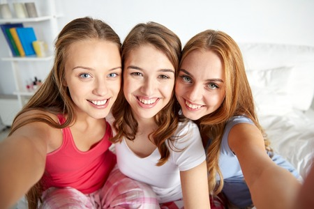 pajama party: friendship, people, pajama party and fun concept - happy friends or teenage girls taking selfie at home