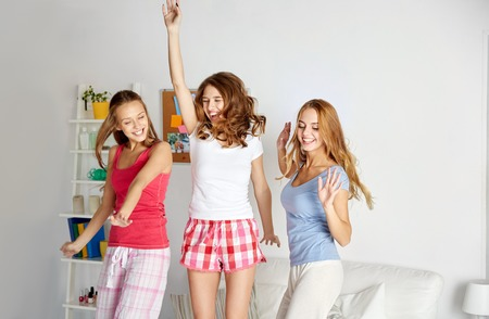 pj's: friendship, people and pajama party concept - happy friends or teenage girls having fun, dancing and jumping on bed at home
