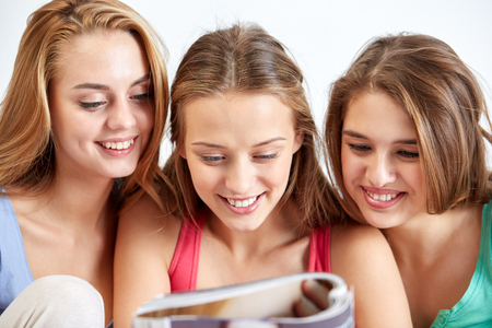 pj's: friendship, people and pajama party concept - happy friends or teenage girls reading magazine at home Stock Photo
