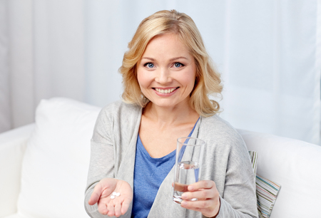 home health care: medicine, health care and people concept - happy middle aged woman with medicine and water glass at home