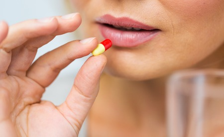 taking medicine: medicine, health care and people concept - close up of woman taking in pill