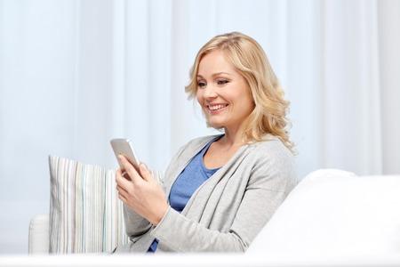 personas, la comunicación, la tecnología y el concepto de Internet - mujer sonriente con los mensajes de texto de teléfonos inteligentes en el hogar