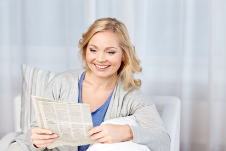 press media: news, press, media, leisure and people concept - smiling woman reading newspaper at home Stock Photo