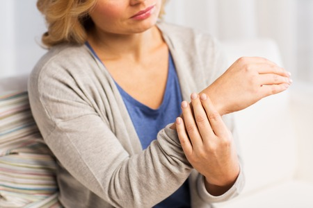 people, healthcare and problem concept - close up of woman suffering from pain in hand at home Stockfoto