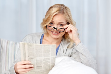 news, press, media, leisure and people concept - woman in eyeglasses reading newspaper at home Stock Photo