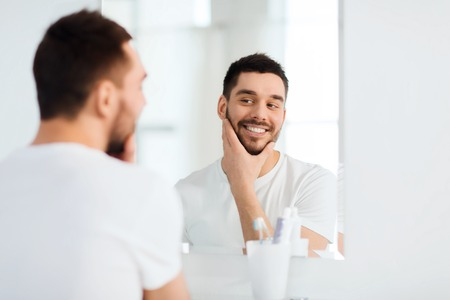 male face: beauty, hygiene and people concept - smiling young man looking to mirror at home bathroom