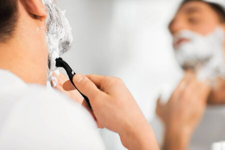 shaving blade: beauty, hygiene, shaving, grooming and people concept - close up of young man looking to mirror and shaving beard with manual razor blade at home bathroom