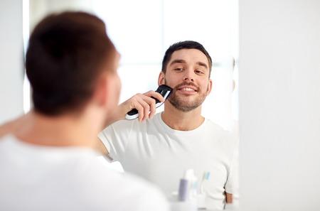 Schönheits-, Hygiene-, Rasierungs-, Pflegen und Leutekonzept - junger Mann, der schaut, um Bart mit Badezimmer des Rasierers oder des elektrischen Rasierers zu Hause zu spiegeln und zu rasieren