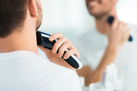 electric trimmer: beauty, shaving, grooming and people concept - close up of young man looking to mirror and shaving beard with trimmer or electric shaver at home bathroom Stock Photo