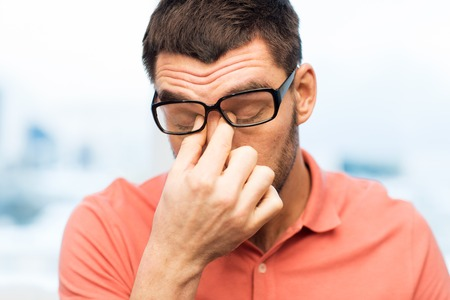 overwork: people, eyesight, stress, overwork and business concept - tired man in eyeglasses rubbing his eyes at home or work