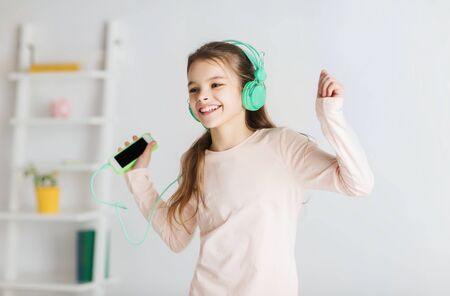 pajama party: people, children, pajama party and technology concept - happy smiling girl in headphones with smartphone and listening to music at home Stock Photo