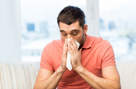 grippe: health care, flu, allergy, hygiene and people concept -sick man blowing nose to paper napkin at home