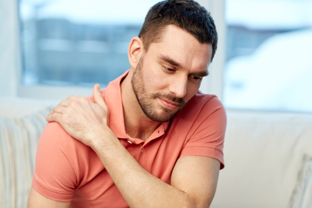 unhappy people: people, healthcare and problem concept - unhappy man suffering from neck or shoulder pain at home
