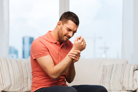unhappy people: people, healthcare and problem concept - unhappy man suffering from pain in hand at home