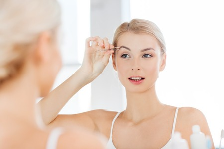 tweezing eyebrow: beauty and people concept - smiling young woman with tweezers tweezing eyebrow and looking to mirror at home bathroom Stock Photo