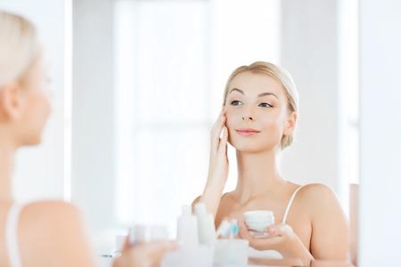 beauté, soins de la peau et les gens concept - jeune femme souriante d'appliquer la crème sur le visage et regardant au miroir à la maison salle de bain