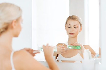 toner: beauty, skin care and people concept - young woman applying lotion to cotton disc for washing her face at bathroom